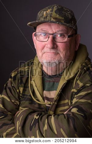 Portrait of a senior elderly old man wearing camouflage clothing and glasses. senior citizen face is happy and smiling.