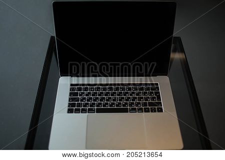 Open laptop computer lying on a wooden table. Copy space screen on a portable net-book