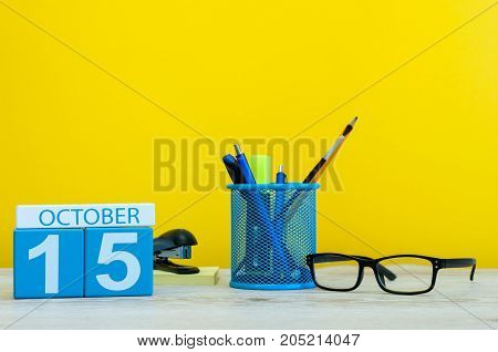 October 15th. Day 15 of october month, wooden color calendar on teacher or student table, yellow background . Autumn time.