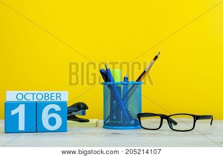 October 16th. Day 16 of october month, wooden color calendar on teacher or student table, yellow background . Autumn time.