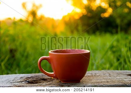 Morning Cup Of Coffee On Wooden Table At Sunrise