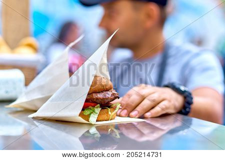 Two hamburgers at the counter of a street cafe, cheese and fried egg on a metal trays on the bar counter waiting to be served. Selective focus, close up. Fast food cafe cuisine. Space for text.