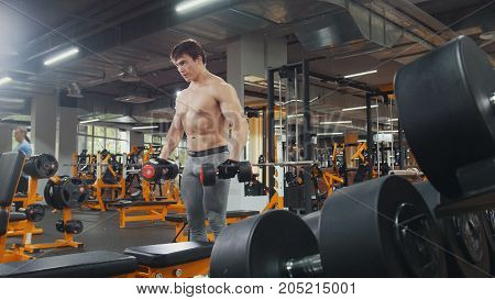 Athlete man lifting dumbbells without shirt in the gym, close up