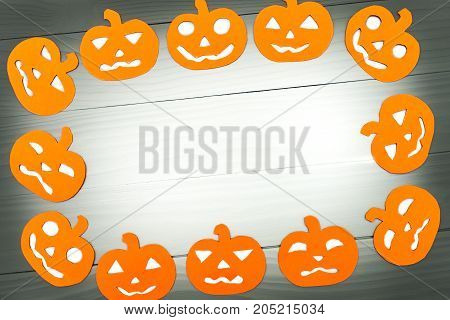 Round frame with different pumpkin paper silhouettes on a gray wooden table. Halloween celebration. Copy space for greetings
