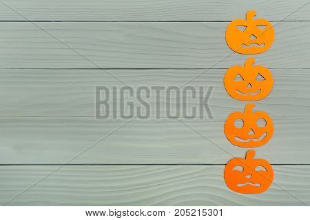 Top view of paper silhouette of four different pumpkin right vertically on grey wooden background. Halloween holiday background. Copy space