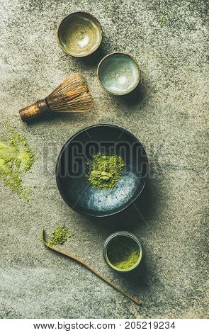 Flat-lay of Japanese tools for brewing matcha tea. Matcha powder in tin can, Chashaku spoon, Chasen bamboo whisk, Chawan bowl and ceremony cups over concrete background, top view, vertical composition
