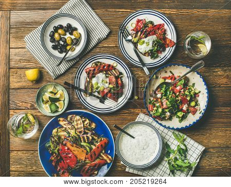 Flat-lay of healthy dinner table setting. Fresh salad, grilled vegetables with yogurt and dill sauce, pickled olives, lemon water over wooden background, top view. Clean eating, vegetarian food