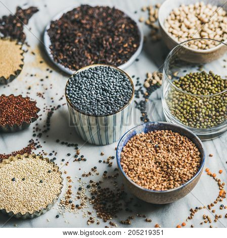 Various raw uncooked grains, beans, cereals in bowls, cups and glass for healthy cooking over marble background, selective focus, square crop. Clean eating, dieting, healthy, detox, vegan food concept