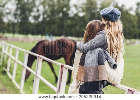 Mother And Daughter At Paddock With Horse