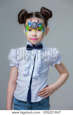 Little girl with a picture of the rabbit on the face on gray background