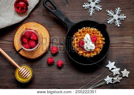 Christmas breakfast with waffles and berries top view on wooden background