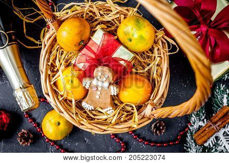Christmas gifts and champagne with tangerines top view on dark background