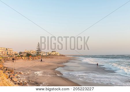 SWAKOPMUND NAMIBIA - JUNE 30 2017: A beach scene with holiday apartments and tourists at sunset in Swakopmund in the Namib Desert on the Atlantic Coast of Namibia