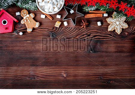 Christmas gingerbread, spruce branches on dark wooden background top view.