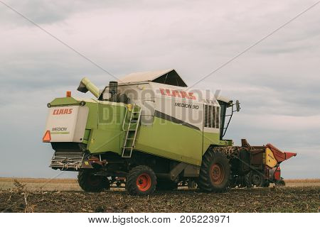 ZRENJANIN SERBIA - SEPTEMBER 19 2017: Combine harvester auger unloading harvested corn into tractor trailer. Lower maize crop yield expected this year in Vojvodina region due to drought during summer.