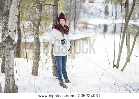 A Young happy pregnant woman in snowy forest