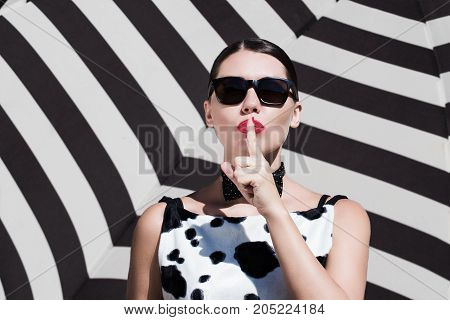 Stylish beautiful woman with sunglasses and bright painted lips showing secret gesture next to a striped background