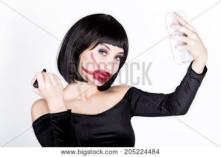 beautiful young woman applying dark red lipstick, ugly dyed lips.