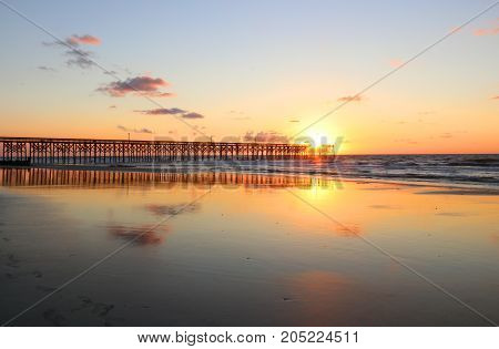Golden sunrise over the ocean. Atlantic ocean landscape with a wooden pier in Myrtle Beach area South Carolina USA.