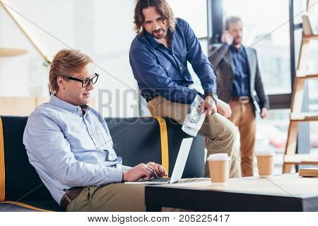 businessman in eyeglasses using laptop while colleague holding newspaper and sitting near by