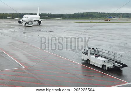 Airport runaway with airplane on a rainy day. Travel background