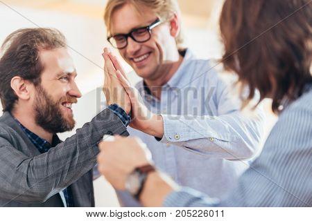 Smiling Men Giving High Five