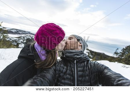 Image of happy couple young loving having fun in snowy mountains, handsome man kiss his cute girlfriend