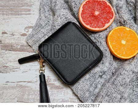 Little Black Womens Purse, Sweater And Citrus On A Wooden Background. Fashion Concept