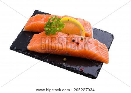 Two pieces of salmon raw fish decorated with lemon sliceparsley leaf and pepper spice lay on black slate isolated on white.