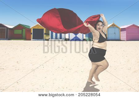 Attractive obese woman wearing swimwear and running at the coast while holding a red scarf
