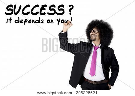 Young Afro businessman with curly hair writing Success depends on you. Isolated on white background