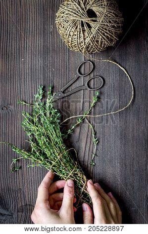 thyme on wooden background with hands top view.