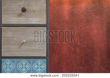 Picture of old handmade drawer organizer with red textured wall at the background