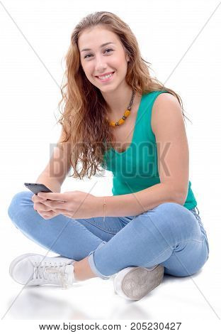 a smiling woman in green casual smart clothing sitting crossed legs holding smartphone