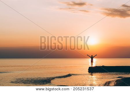 Young woman standing with raised arms looking in sunset