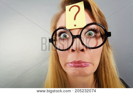 Crazy wondering face expression concept. Wierdo nerd woman having question mark on forehead and geek eyeglasses. poster
