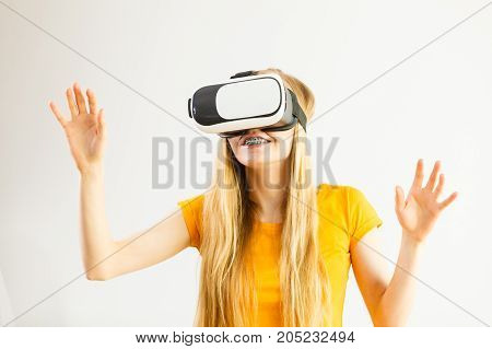 Young woman wearing virtual reality goggles headset vr box stretching arms. Connection technology new generation and progress concept. Studio shot on gray