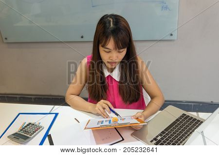 Young businessman checking the sales report of company carefully