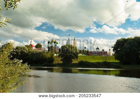 Kolomna Moscow Region. Beautiful Landscape Of Various Temples And Belltower On Assumption Cathedral Square Under Blue Sky With Dramatic Clouds By Embankment Reflection River In Sunny Summer Day.