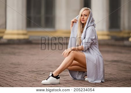 Beautiful fitness girl with perfect body shapes sitting in the grey sports cloak on the street of the evening city.