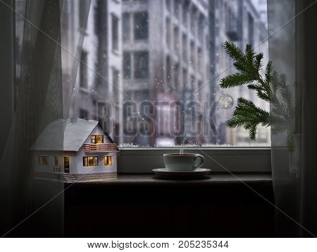 On the windowsill fairy house coffee and a fir branch. Outside the city snow. Winter holiday still life. Christmas or New year