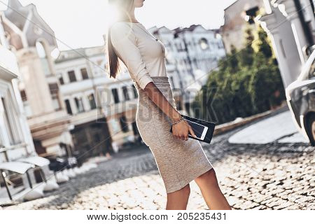 Businesswoman on the go. Close-up of young woman carrying her smart phone and wallet while walking outdoors