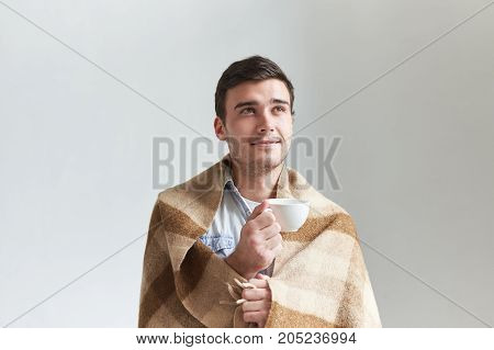 People leisure and relaxation concept. Studio shot of good looking positive male wrapped in wool blanket holding white mug while relaxing indoors drinking herbal tea having joyful happy smile