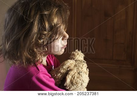 A sad child with a favorite soft toy