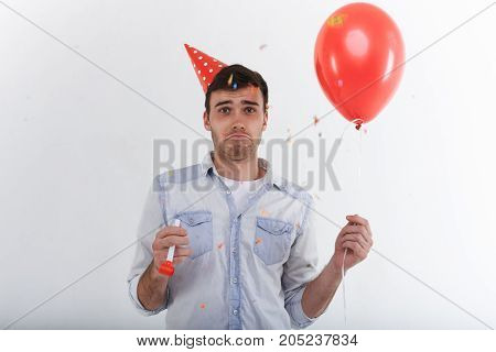 Human emotions. Sad unhappy young European male with stubble having displeased disappointed look feeling lonely on his birthday party holding red party horn and helium balloon in his hands