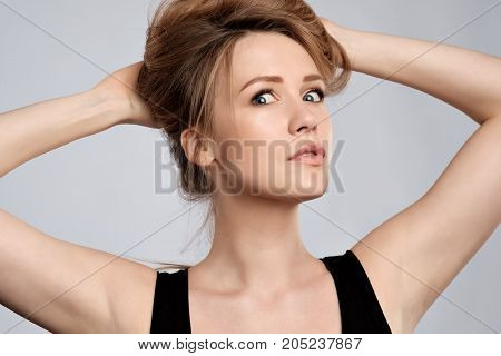 Beauty blonde woman with professional perfect makeup. Looking with surprise at camera. Hands holding hair. Shocked emotion on face