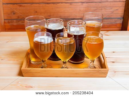 Beer glasses and beer mugs on wooden table. Selective focus