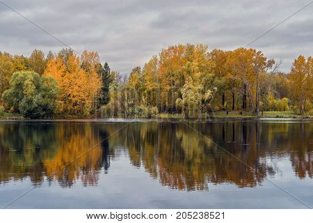 The lake reflecting the cloudy sky and autumnal foliage trees growing on the shore