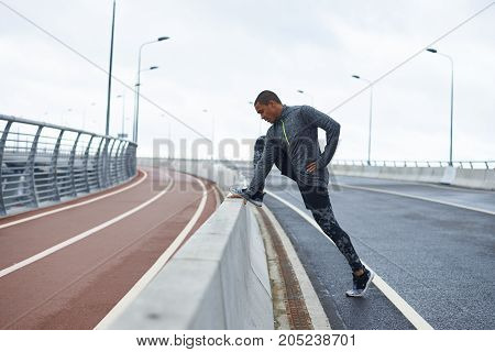 Strength and endurance concept. Profile shot of young dark-skinned runner with muscular legs stretching muscles after running workout outdoors. Black male training at stadium on his day off
