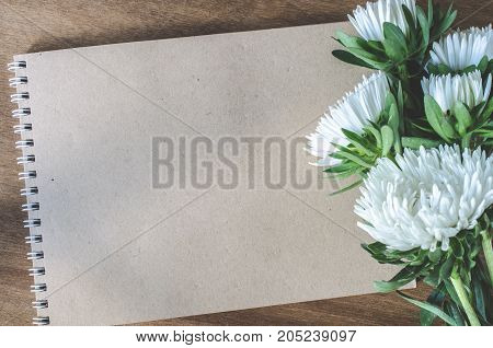 Flat lay of blank brown notebook with autumn flowers on wooden table. Copy space.